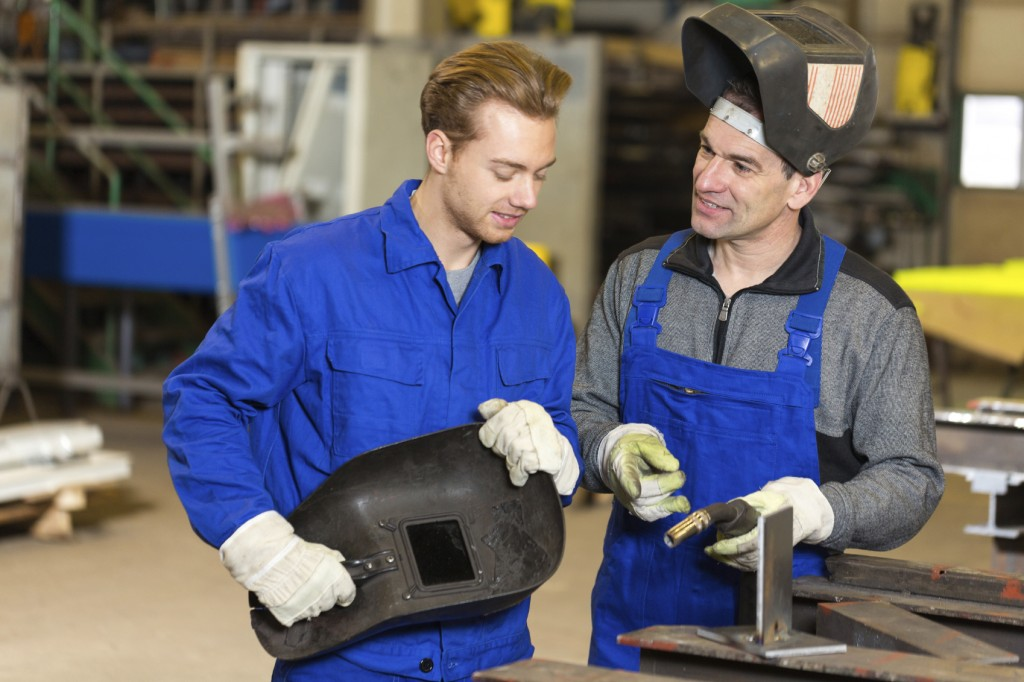 Instructor teaching trainee or worker how to weld metal